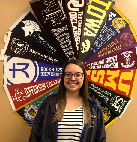 Ms. Lauren Ficker poses in front of her circle of college banners