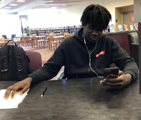 Jeremiah Williams (12) focuses on his phone rather than doing his math homework in the library.