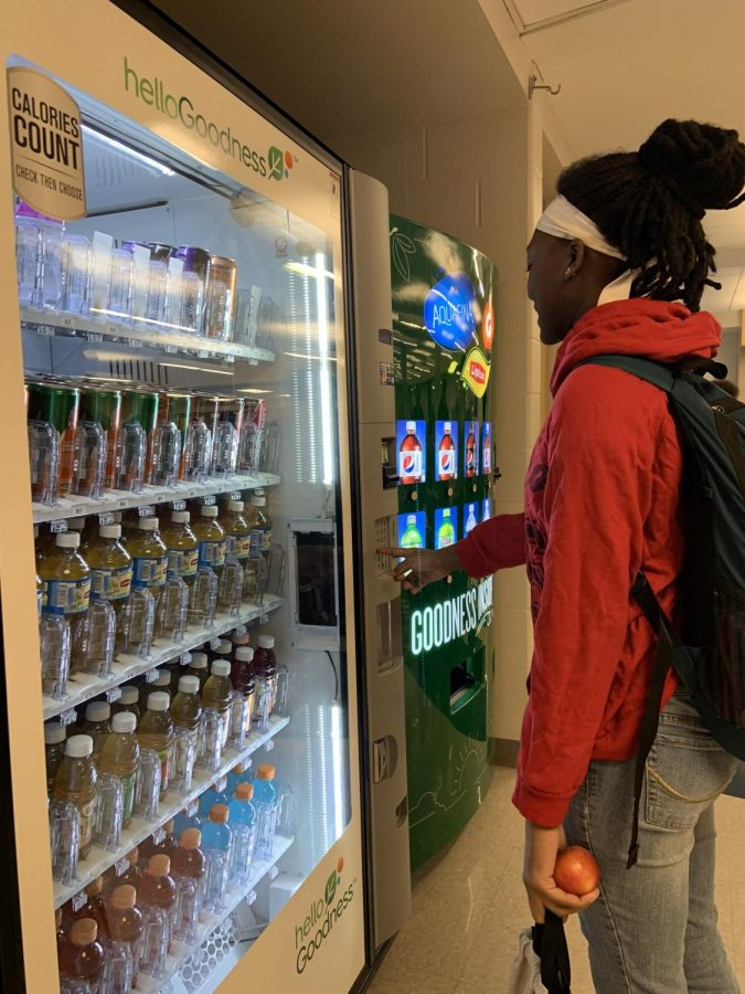 A student gets a caffeinated drink from the vending machine